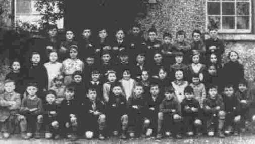 Photograph: Here, a very young Seamus Ludlow is seen in a group photograph of children taken at Faughart National School, in the late 1930s. Seamus is third from extreme right in the top row. His sister Kathleen can also be seen, second from left in the second row.